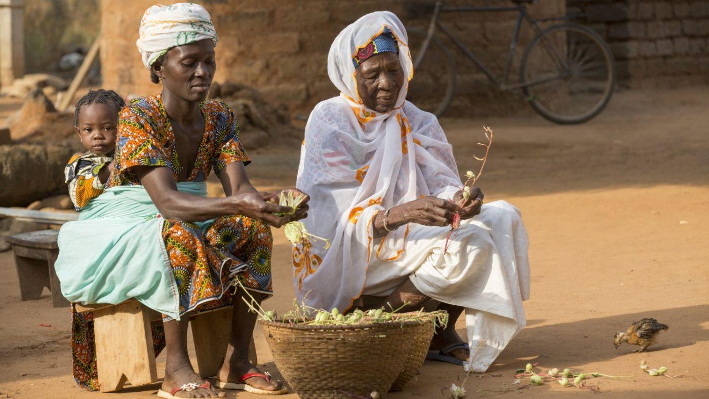 Una donna seduta tiene sulla schiena una bambina e accanto a lei un'altra donna. Entrambe hanno tra le mani dei fiori secchi.
