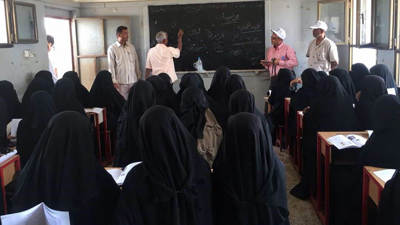 Un gruppo di donne con il velo nero sui banchi di scuola ascoltano un uomo che parla alla lavagna. Con lui ci sono altri tre uomini.