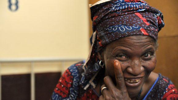 Una donna sorride e indica il suo occhio con un dito.