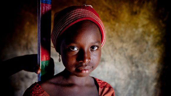 Una bambina vestita di rosso sorride. Alle sue spalle il bastone per la misurazione.