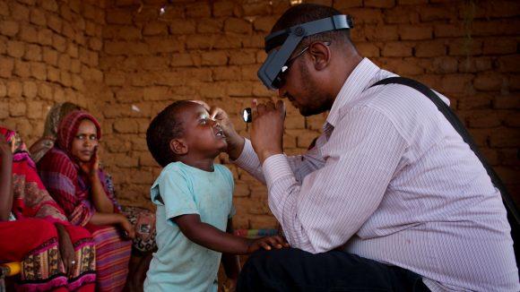 un dottore punta una luce negli occhi di un bambino e lo visita.