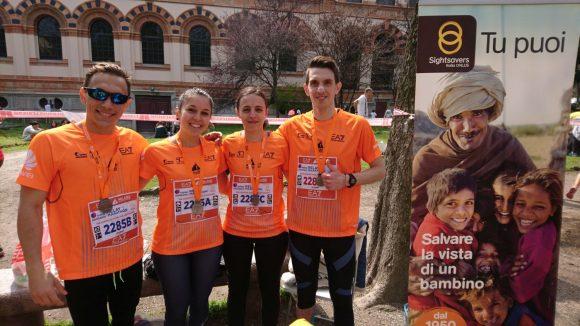 Quattro ragazzi con le pettorine di Sightsavers dopo la maratona di Milano
