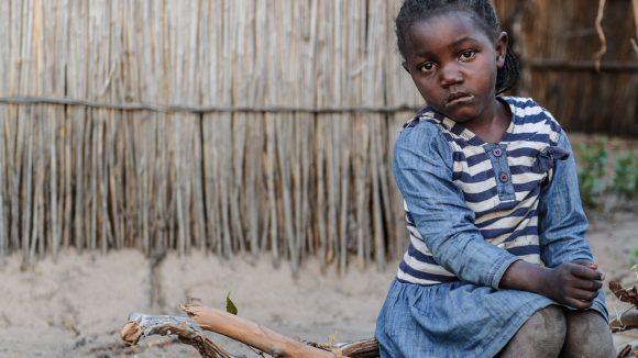 Una bambina seduta sul tronco di un albero guarda di fronte a sè con lo sguardo triste.