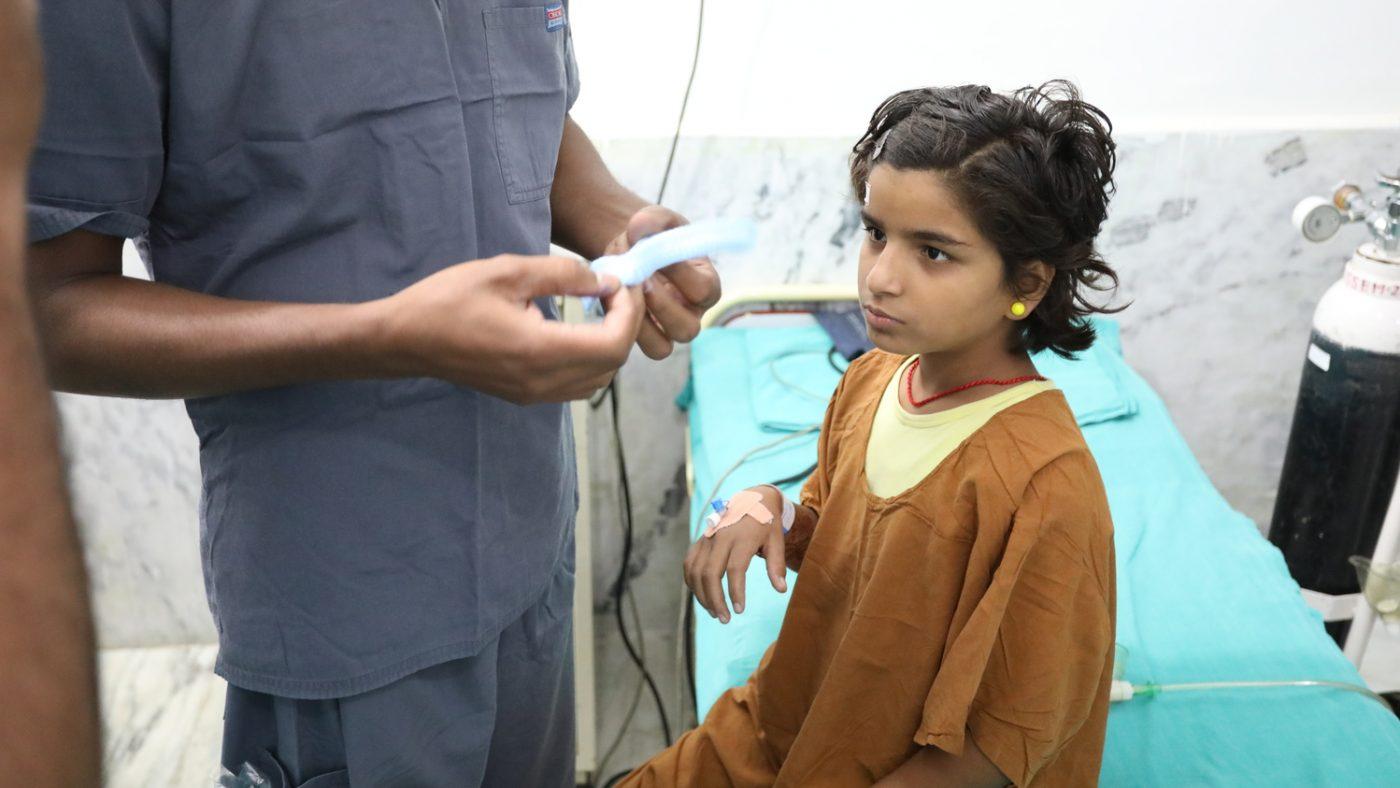 Una bambina è seduta sul lettino di ospedale e avvanto a lei un infermiere.