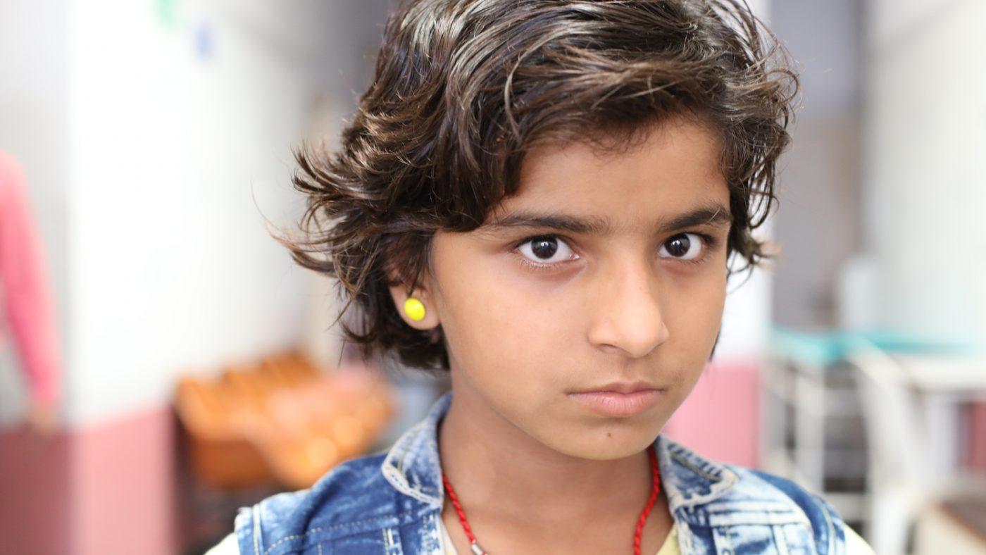 Una bambina con gli orecchini gialli guarda davanti a sè.