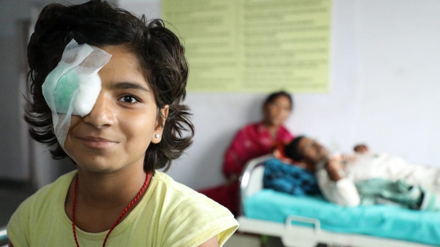 Una bambina ha la benda sull occhio e sorride.