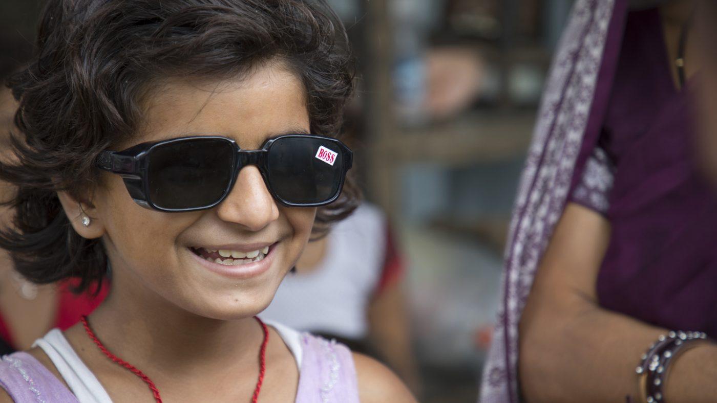 Una bimba indossa gli occhiale da sole e sorride.