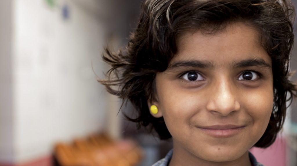 Una bambina sorride e guarda davanti a sè.