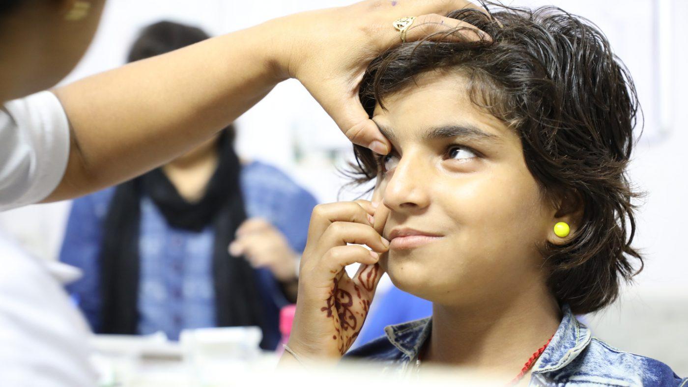 La mano di un dottore tocca gli occhi di una bambina per visitarla.