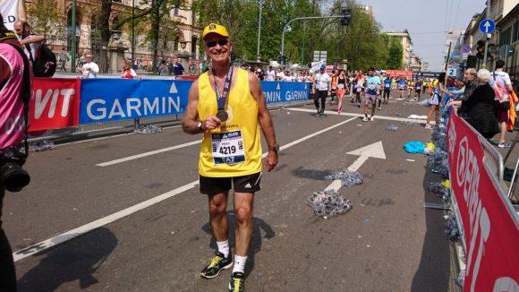 Un maratoneta con la maglietta di Sightsavers sorride e tiene la sua medaglia in mano dopo la corsa