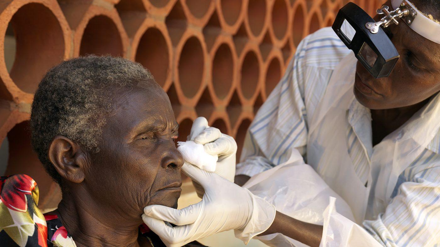 Una persona anziana si fa pulire l'occhio destro da un infermiere oftalmico