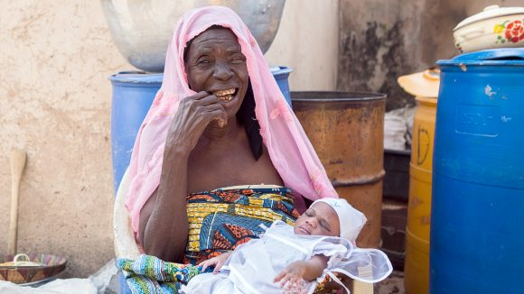 Rahinatu tiene la sua nipotina e sorride dopo l'intervento chirurgico del tracoma