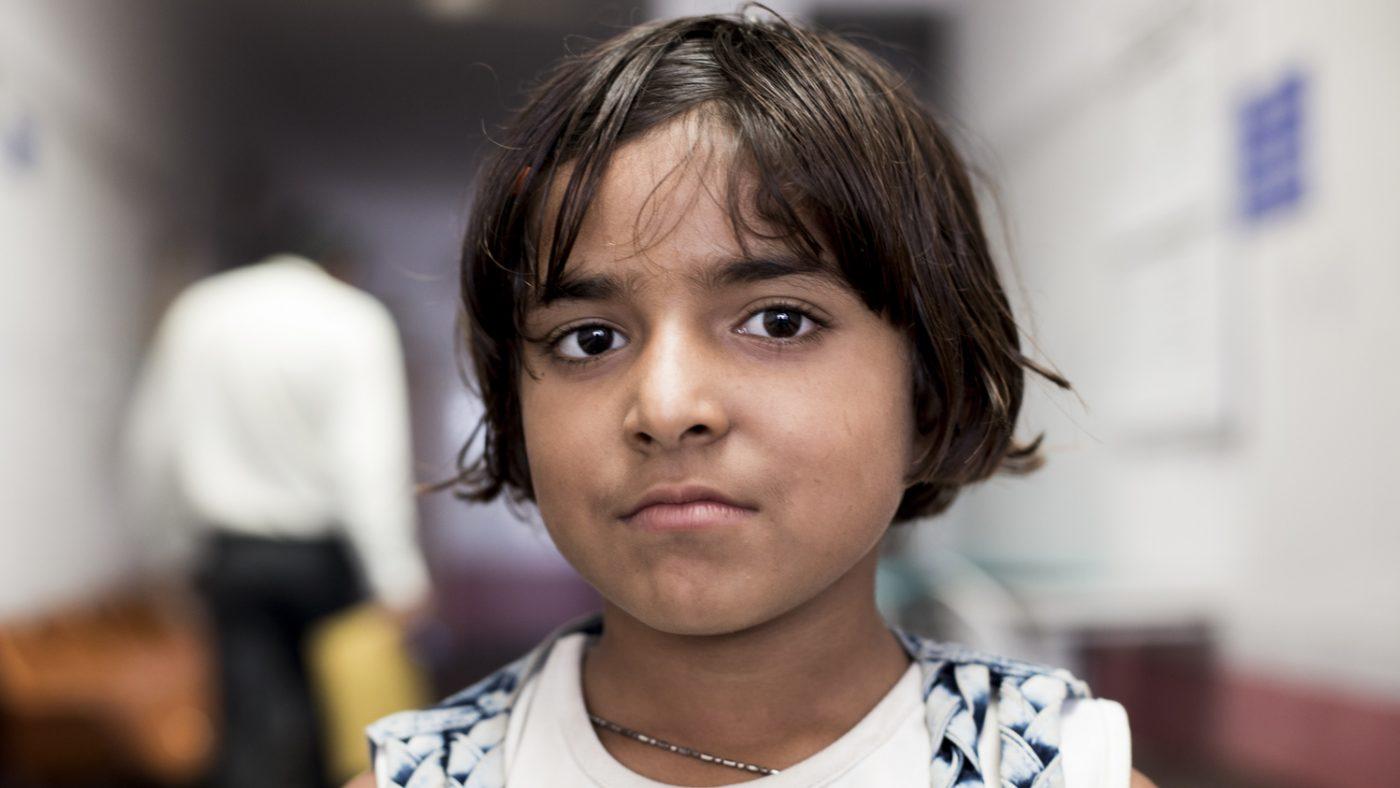 Una bambina guarda davanti a sè con un espressione seria.