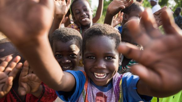 Dei bambini sorridenti in gruppo salutano.