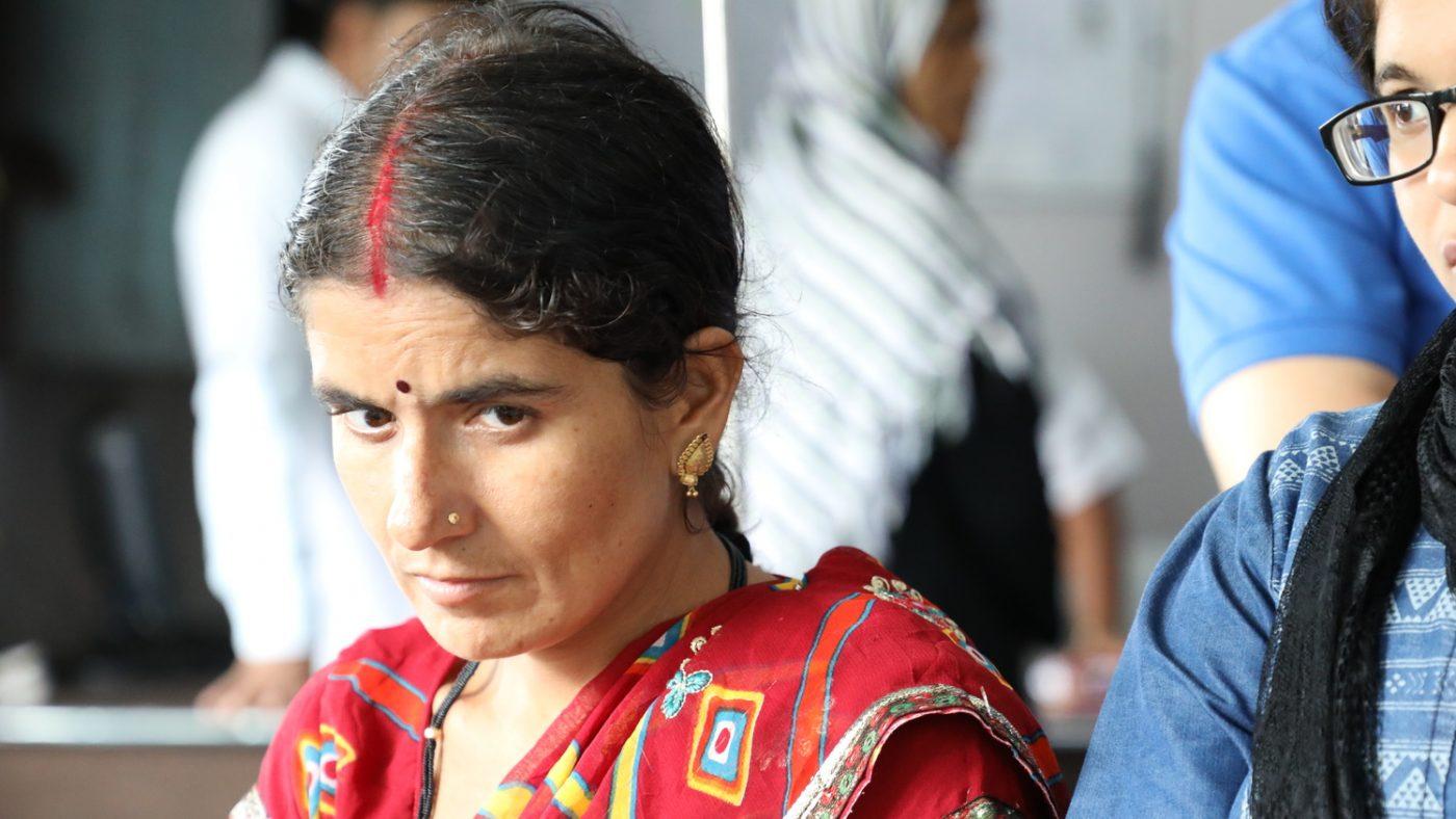 Una donna vestita di rosso guarda davanti a sè con un'espressione triste.