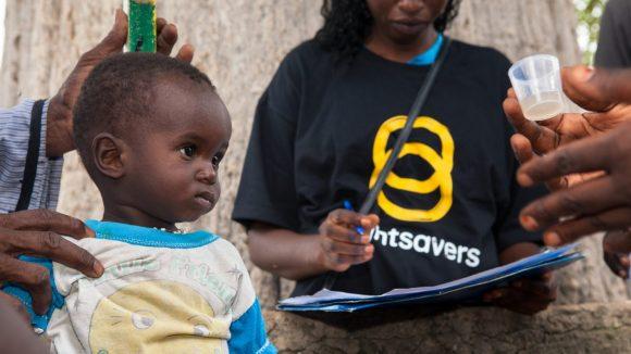 Un bambino si fa prendere le misure con un bastone e una donna con la maglietta di Sightsavers segna i risultati, il bambino guarda un bicchierino che contiene la medicina