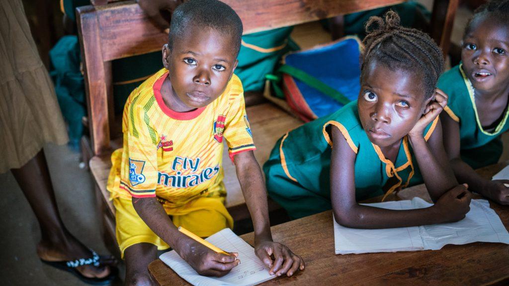 Due bambini con problemi agli occhi sono seduti al banco e guardano davanti a loro.