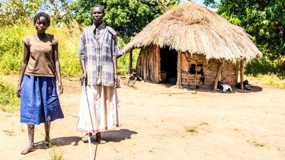 Ayenyo tiene in mano il bastone bianco e cammina a fianco di sua figlia Lawino.