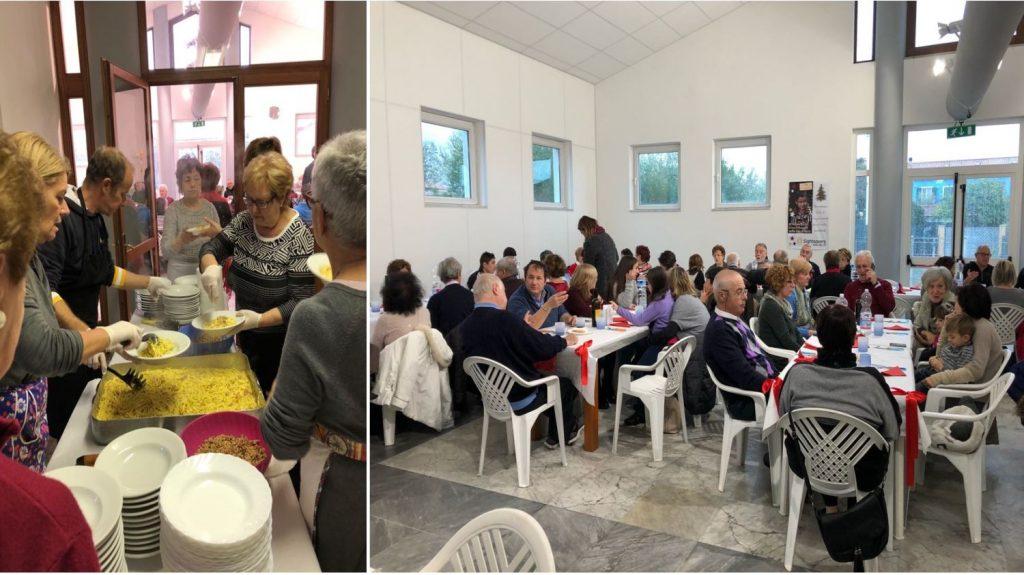 A sinistra delle persone stanno distribuiendo la cena agli invitati, a destra si vedono tutte le persone sedute a tavola durante la cena