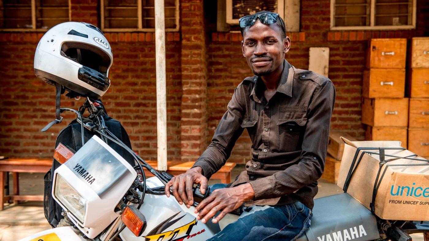 Madalitso sorride in sella alla sua motocicletta.