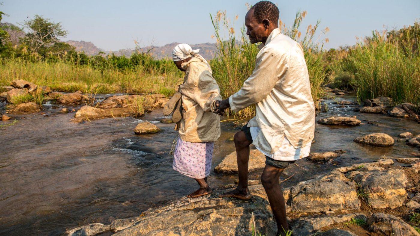 La moglie di Winesi lo tiene per mano per guidarlo mentre attraversano il fiume.