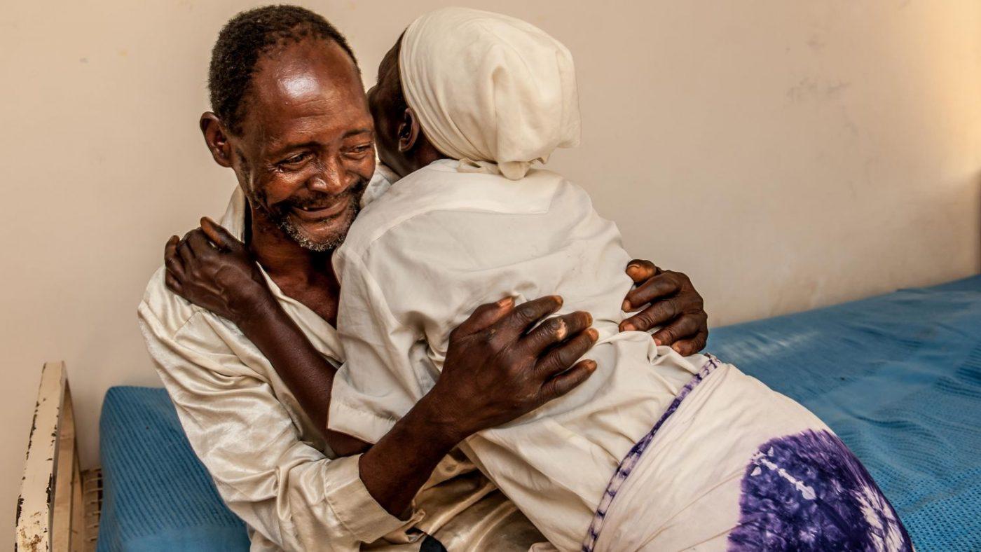 La moglie di Winesi lo abbraccia sul lettino dell'ospedale dove è stato operato.