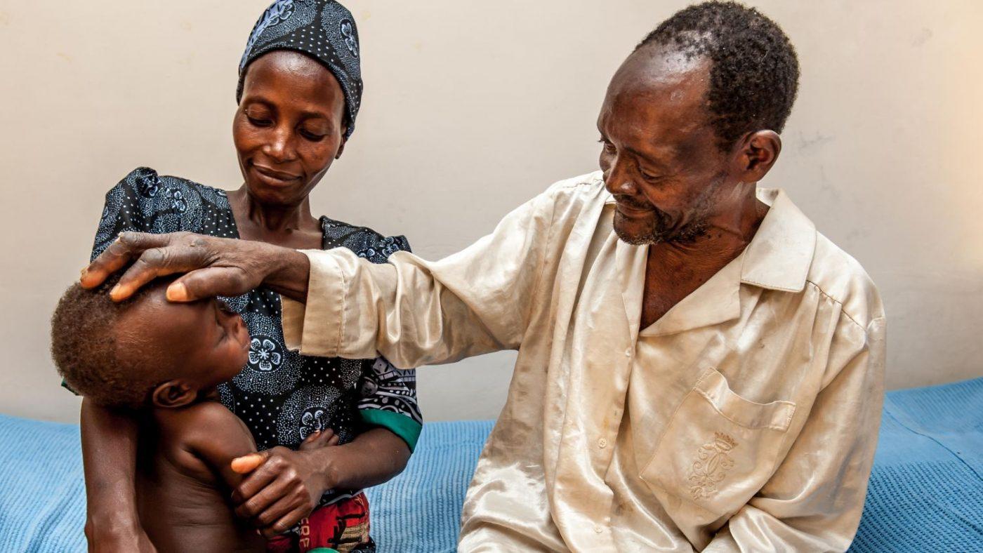 Winesi vede il suo nipotino per la prima volta. Accanto a lui seduti ci sono sua figlia e in braccio il suo bambino.