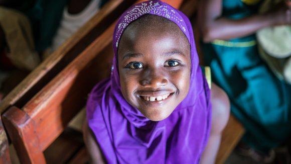 Una bambina con il velo viola sorride.
