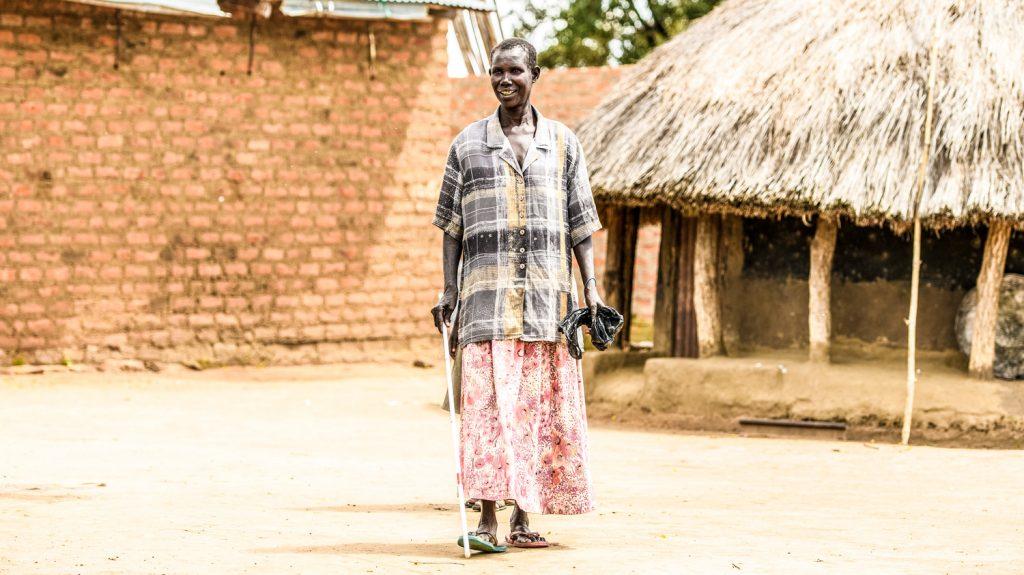 Ayenyo ripresa a figura intera cammina da sola con il suo bastone bianco.