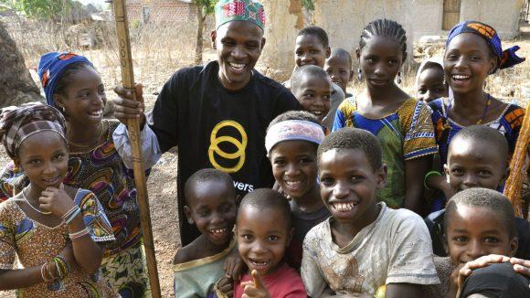 Un volontario di Sightsavers con il bastone circondato da bambini sorridenti.