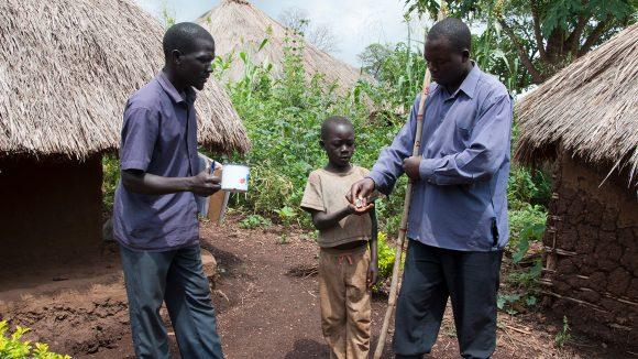 Due volontati distribuiscono il trattamento a un ragazzino.
