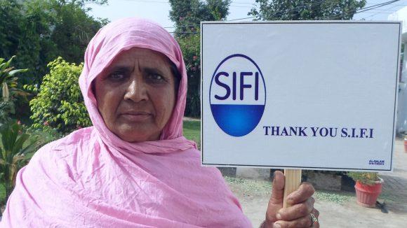 Una donna tiene in mano un cartello con il logo della azienda SIFI che sostiene il lavoro di Sightsavers.