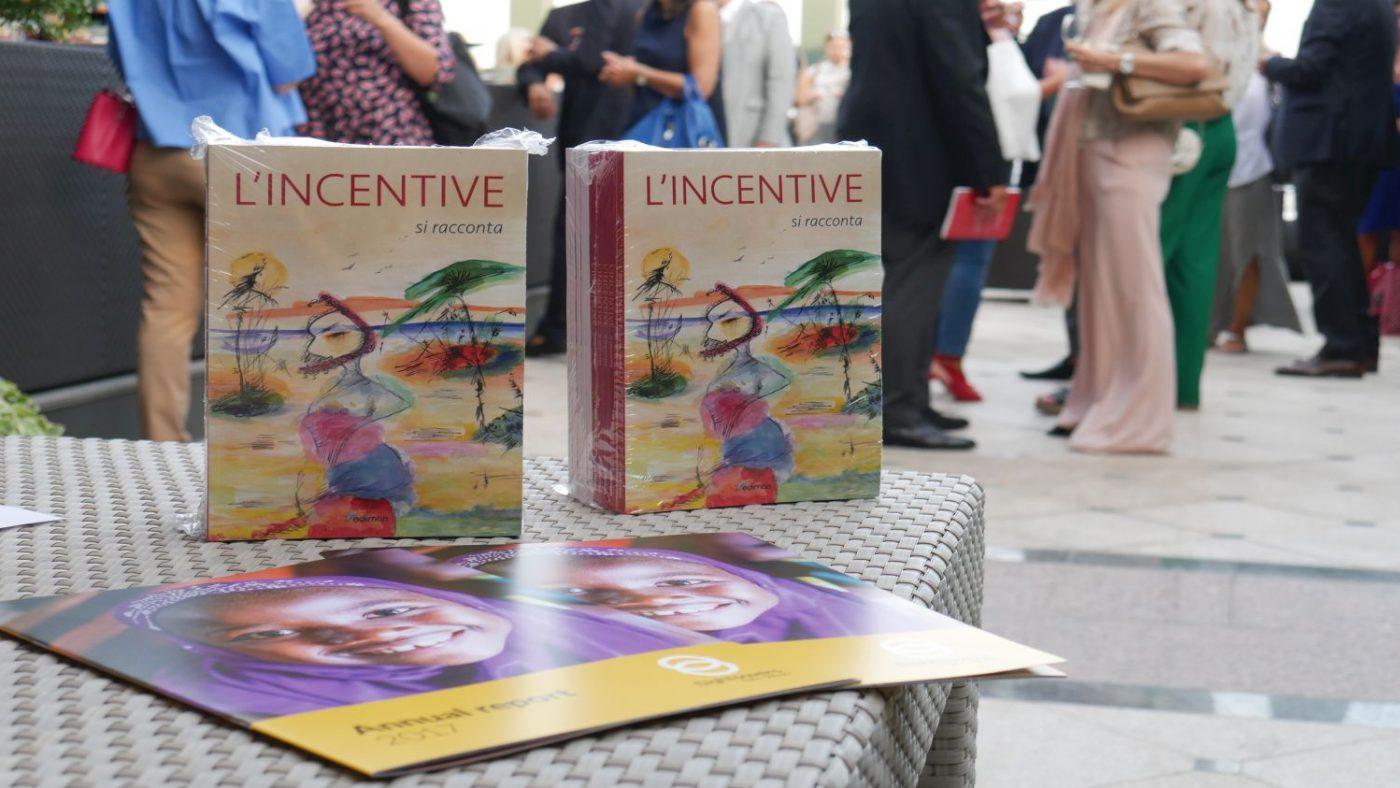 Al primo piano ci sono delle brochure di Sightsavers e degli esemplari del libro, dietro delle persone stanno parlando tra di loro