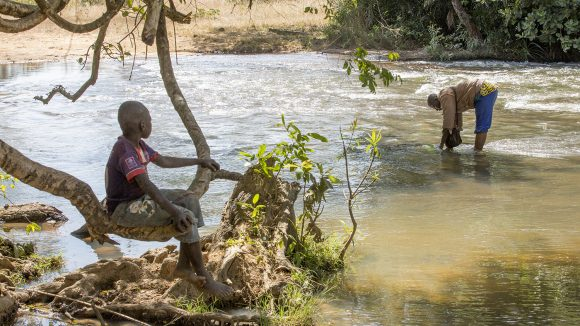 Due uomini stanno catturando delle mosche in un fiume che scorre velocemente