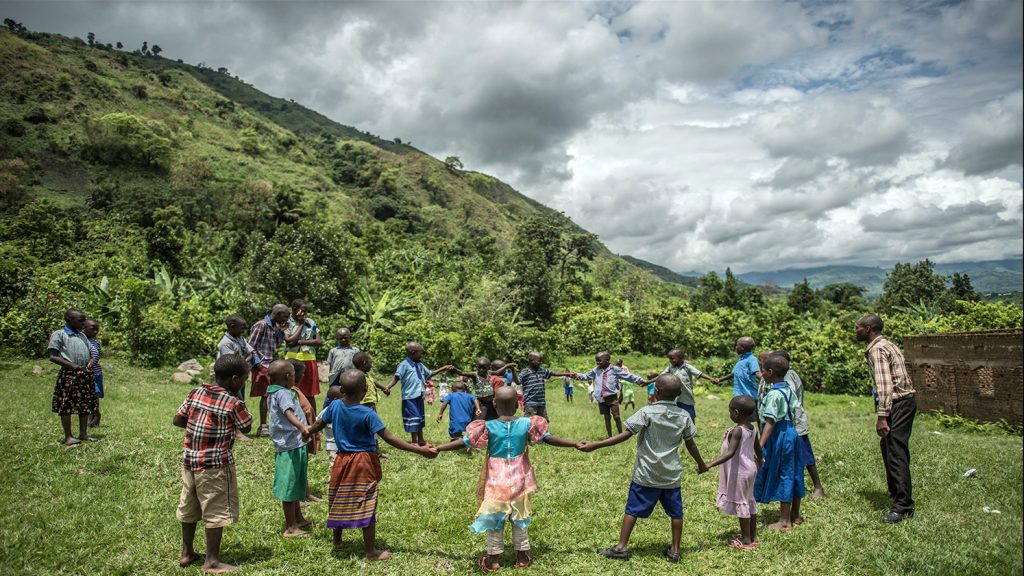A group of children hold hands in a circle in a school in Uganda, with a backdrop of lush green hills.