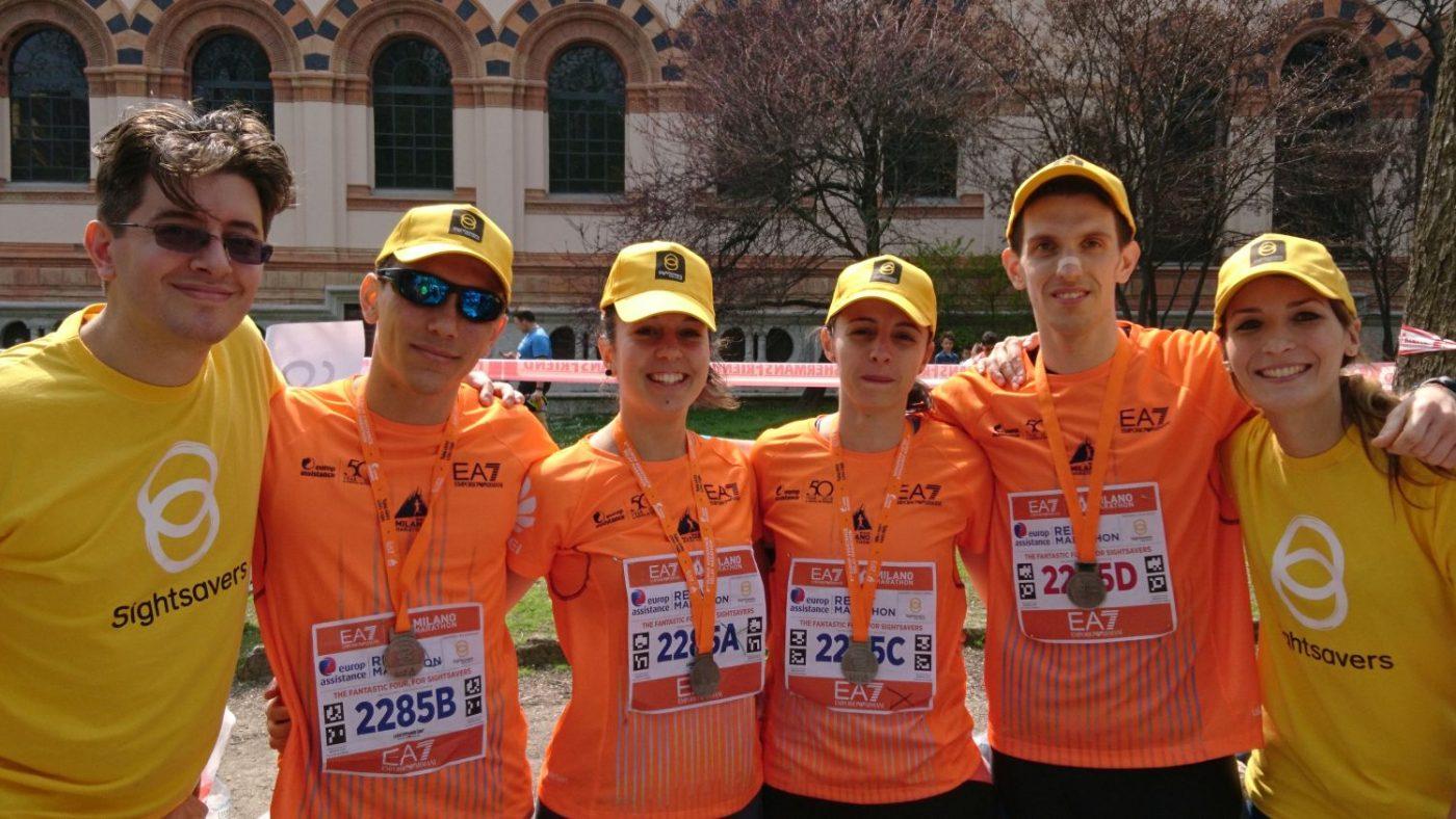 Tre uomini e tre donne stanno guardando davanti a loro indossano la pettorina della maratona e la maglietta di Sightsavers