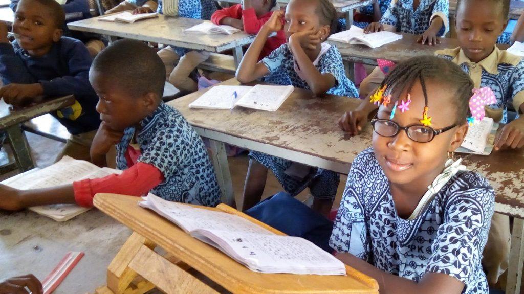 Una bambina con gli occhiali da vista sorride seduta in classe con i suoi compagni.