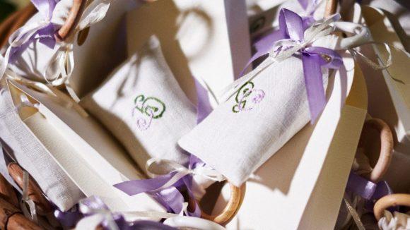 cestino con delle scatoline portaconfetti e dei sacchetini colorati per un matrimonio
