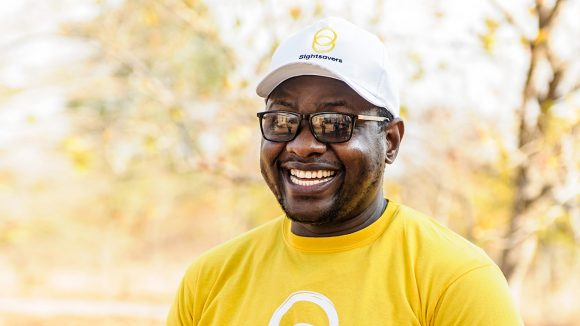 A man smiles, wearing a yellow Sightsavers tshirt.