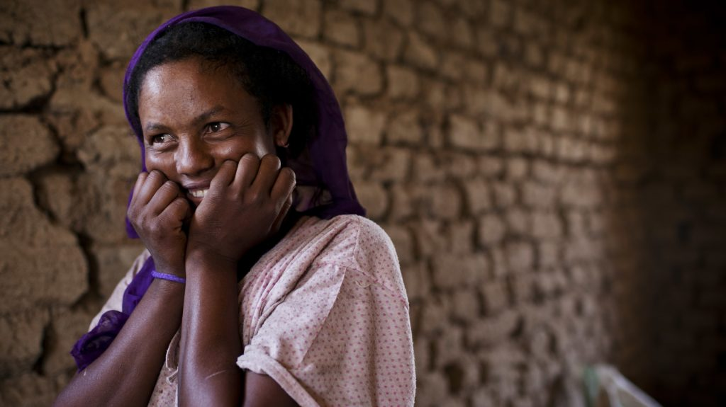 Una donna tiene le mani sul viso e sorride.