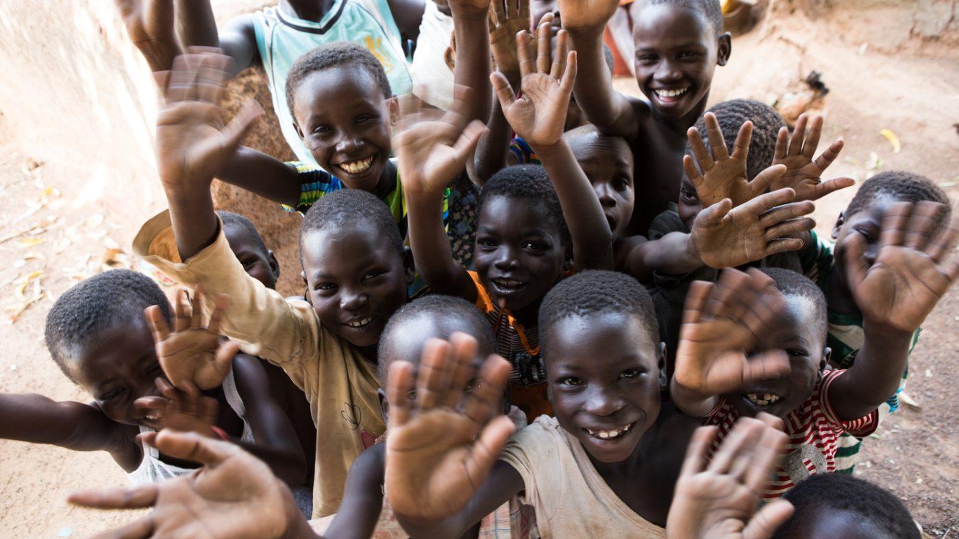Dei bambini sorridono alla fotocamera e salutano.