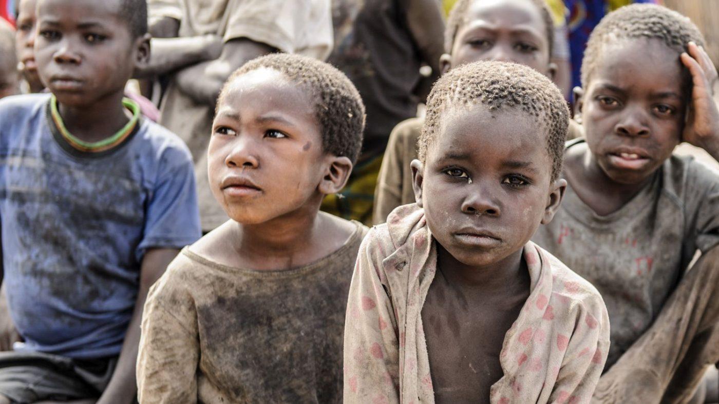 Bambini malati di tracoma e sporchi di polvere guardano davanti a se.
