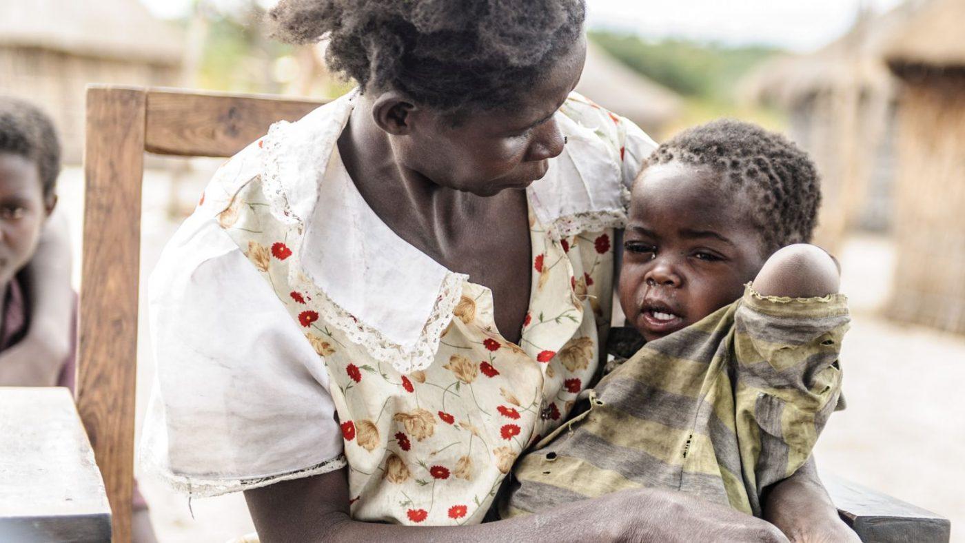 Una bambina piange tra le braccia della sua mamma.