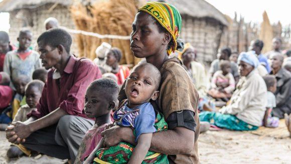 Una mamma con il tracoma tiene in braccio il suo bambino.