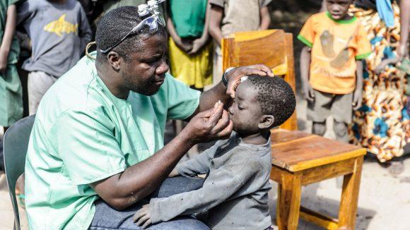 Un dottore visita gli occhi di un bambino.