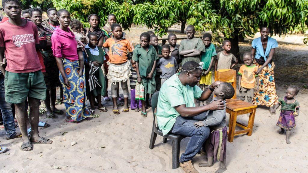Il Dottor Ndalela visita gli occhi di un bambino, mentre altre persone sono intorno a lui a guardare.