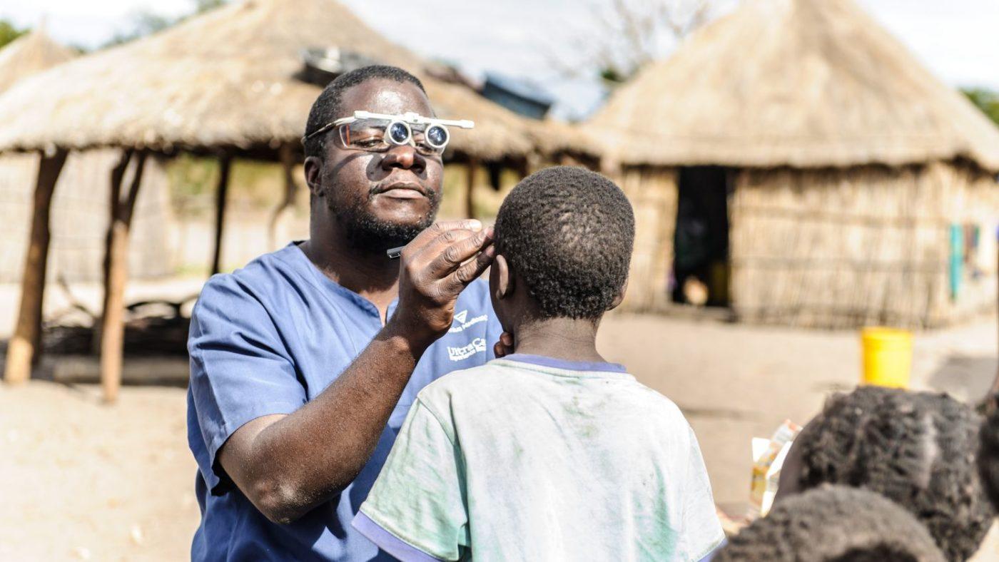 Ndalela indossa degli occhiali speciali mentre visita un bambino.