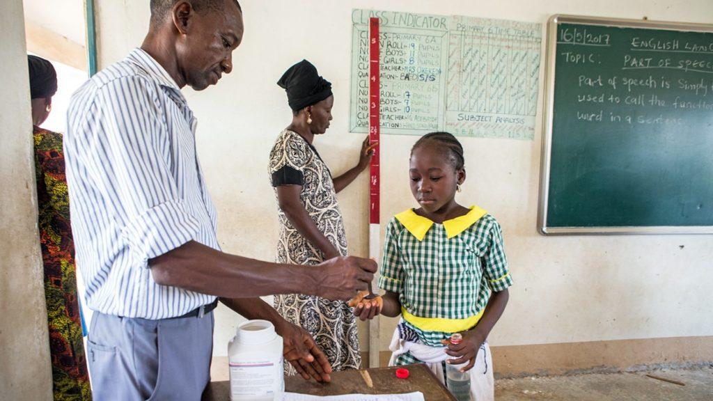 un uomo distribuisce un farmaco ad una bambina a scuola