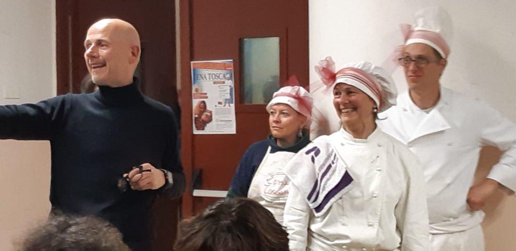 Due uomini e due donne vestitite da cuoco parlano ad un assemblea di persone durante una cena di beneficenza