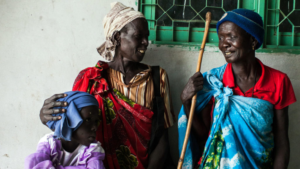 Photo of Nyakaka Yaul Nyuon, 50, who had cataract surgery on her right eye, looks at her twin sister Julius Yaul, and niece Nyakong in Nasir, Upper Nile, South Sudan,
